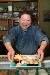 The sushi chef of a small, local sushi place serving a plate of sushi.