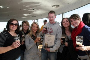 Six people posed for an image with Guinness in hand.  Taken at the top of the Guinness brewery in Dublin.