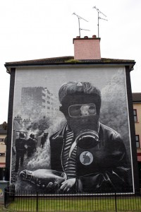 A mural of a man in a gas mask is painted on the side of a house in Derry, Ireland.  Shot while backpacking in 2009