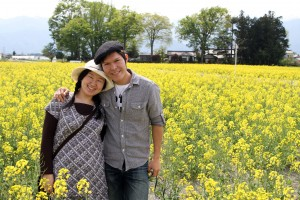 A young Japanese couple in a field of yellow flowers
