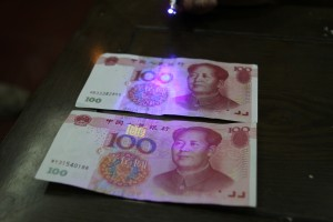 A light shows a box on the real 100 Yuan bill but no box on the counterfeit bill
