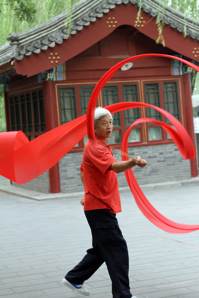 A man practices ribbon twirling (more like dancing) with a very long red piece of cloth