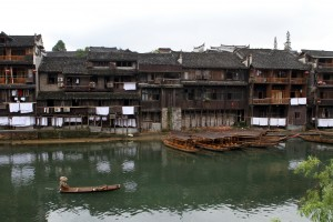 A boatman makes his way along the river with stilted houses in the background.