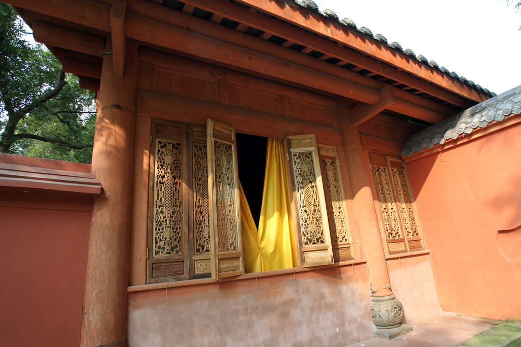 The outside of a temple building with very detailed windows, one of which is open displaying a yellow curtain.
