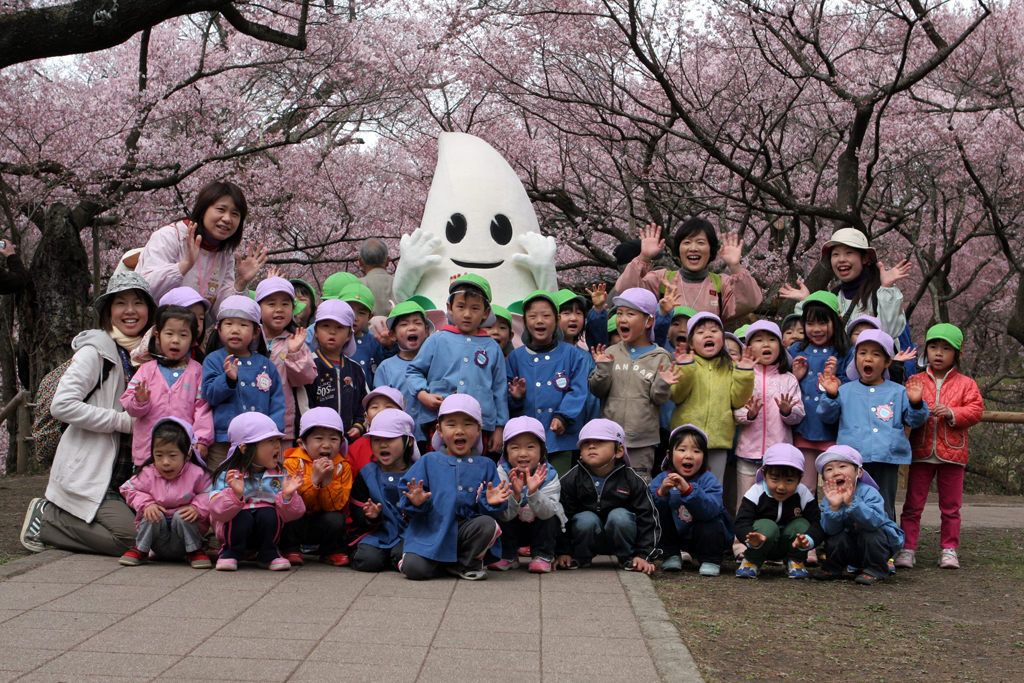 A young group of Japanese kids pose for a picture after viewing cherry blossoms (sakura) in Ina, Japan.