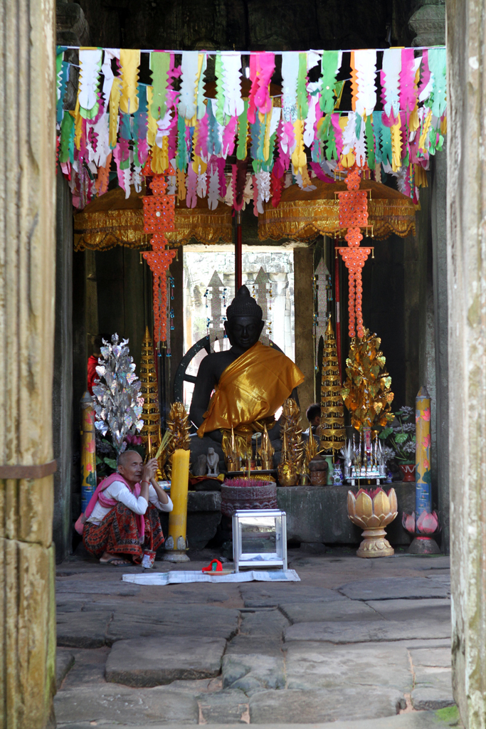 A Cambodian woman squats by a statue of Buddha offering incense to visitors at the Angkor Wat complex in Siem Reap, Cambodia.