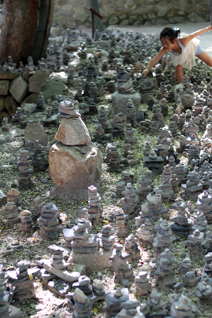 A little girl searches for Won amongst Cairns, human-made piles of stones at a South Korean temple.
