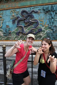 A couple of travelers display their claws in front of the 9 Dragon Wall.