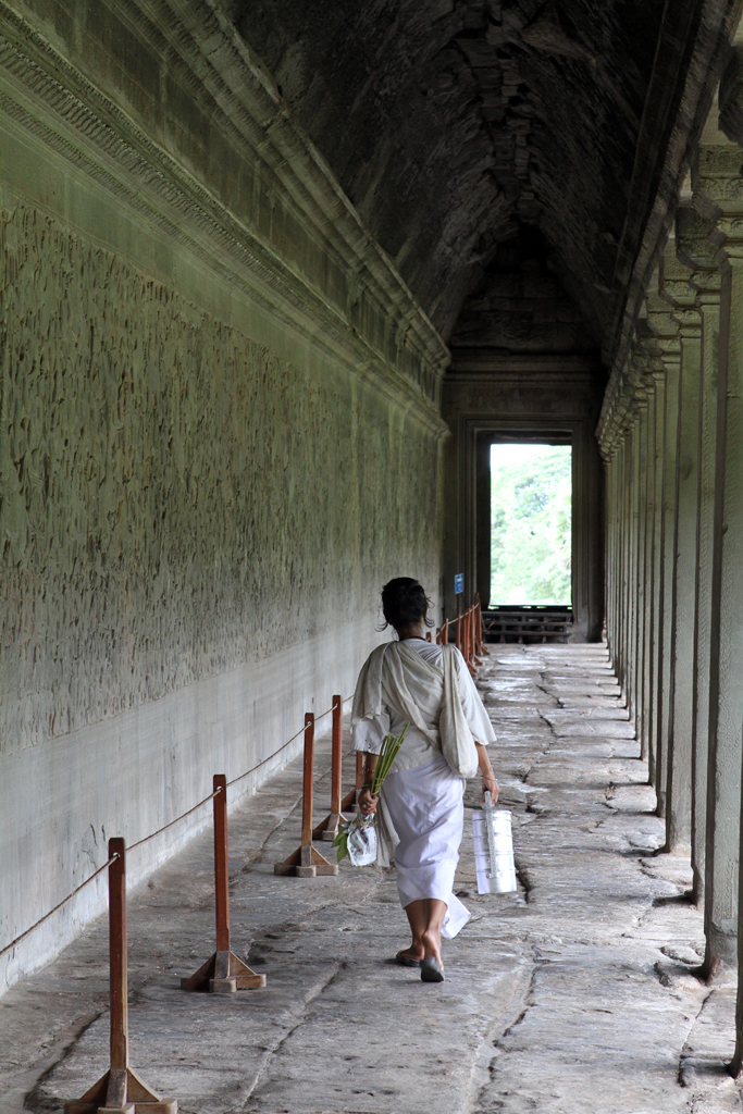 A local woman walks alongside one of many reliefs carved into the walls at the Angkor Wat in Siem Reap, Cambodia.