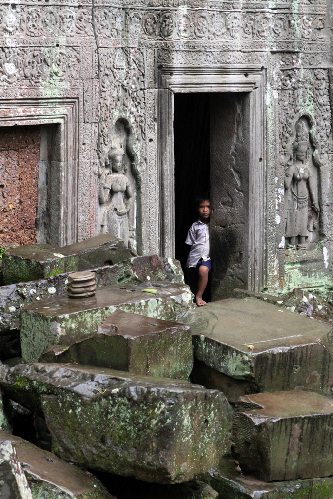 Ta Phrom is known as the Tomb Raider temple, since that is what they based much of the film's imagery on.  Here, a boy peeks out from around a corner while hiding from the rain.