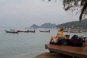 A digital nomad works on the deck of a restaurant in Koh Tao, Thailand.
