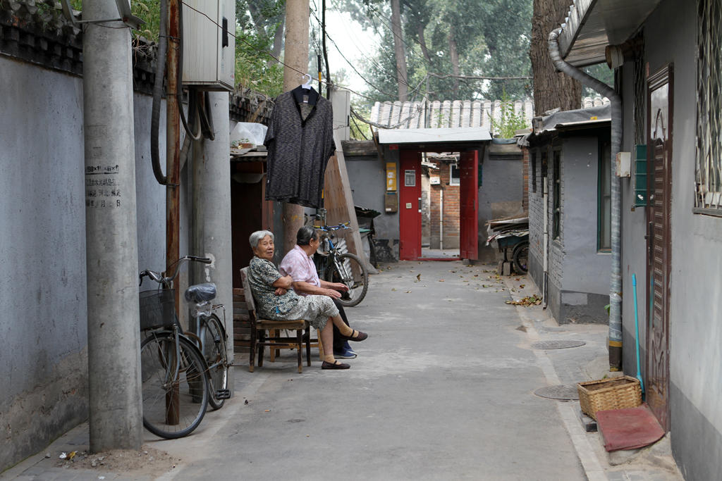 A couple of aged Chinese woman laze the day away down a small street in Beijing.