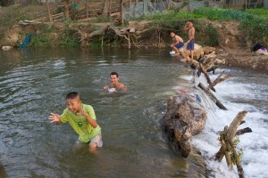 The children of our local host play in the river with the flashpackers that were invited to diner.