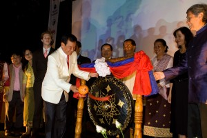 A representative from the Laos government hits a gong marking the start of the festival.