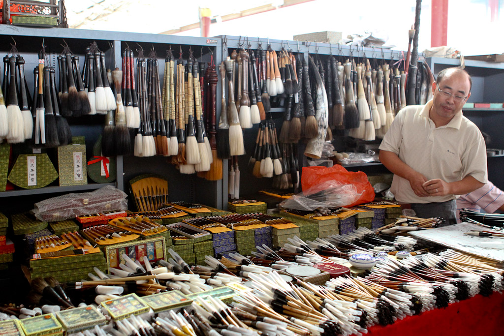 A market trader specializing in paint brushes of many, many sizes.
