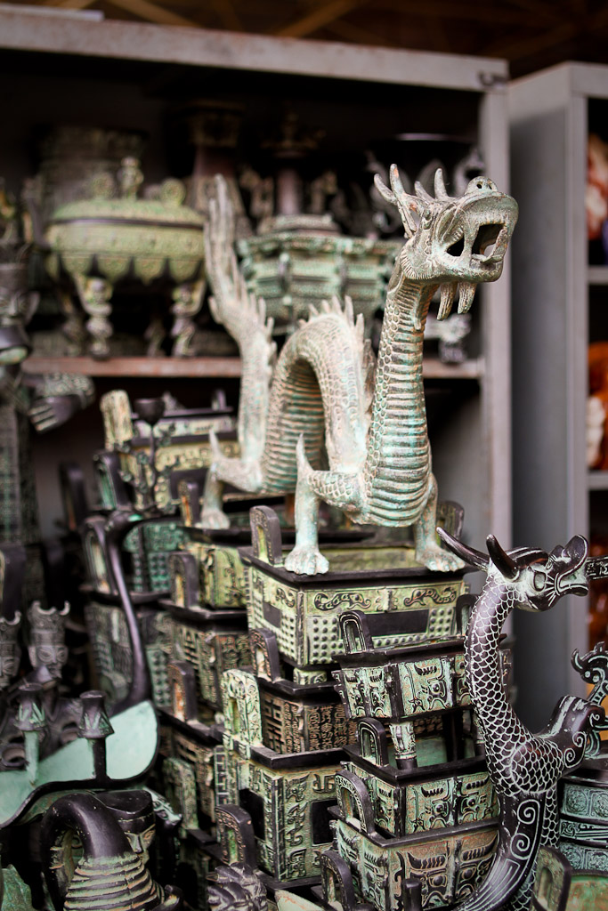 A green dragon statuette sits atop chests at this stall in the Panjiayuan Flea Market