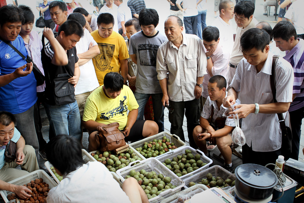 A group gathers around a walnut stall seeking the perfect pair