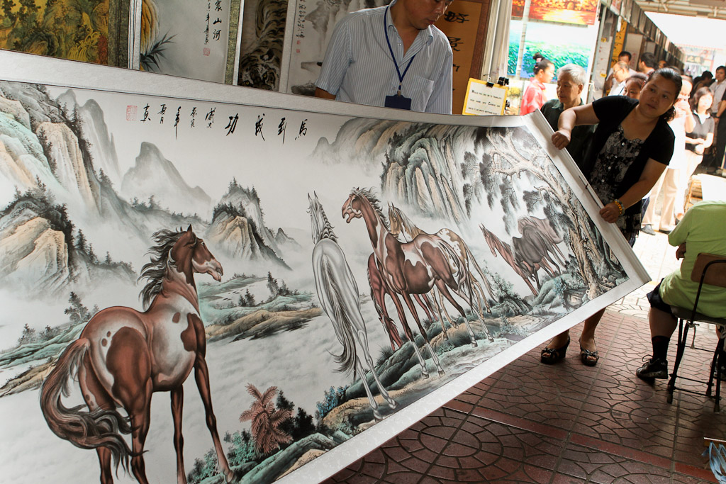 A large landscape painting of horses is unrolled in the art section of the Panjiayuan Flea Market.