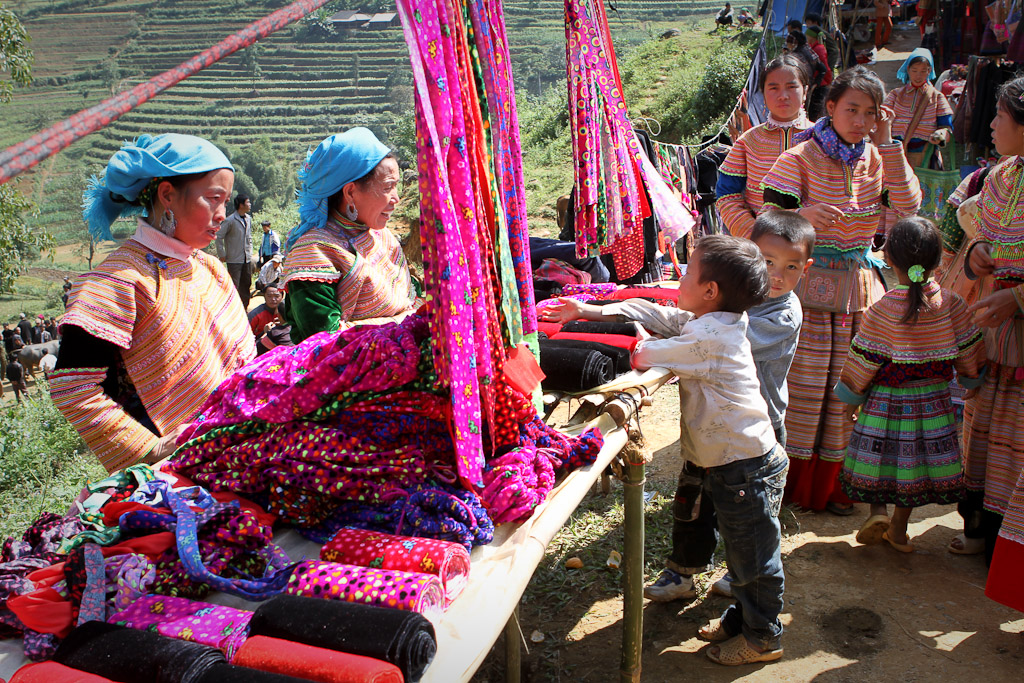 A market stall sells colorful fabrics with terraced fields cut into the hills in the background.