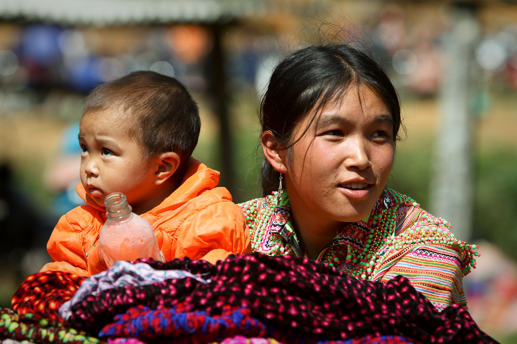 A young Flower Hmong woman watches her little brother while waiting on customers.