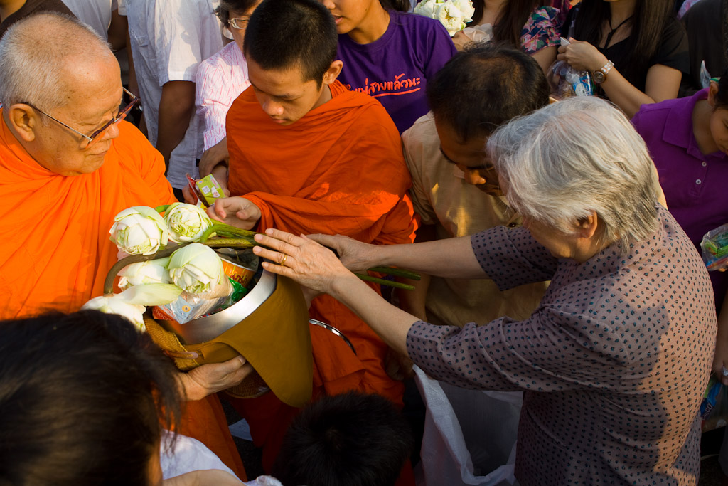 A woman gives alms to the elder monk at the alms presentation during the Songkran Festival in Chiang Mai.