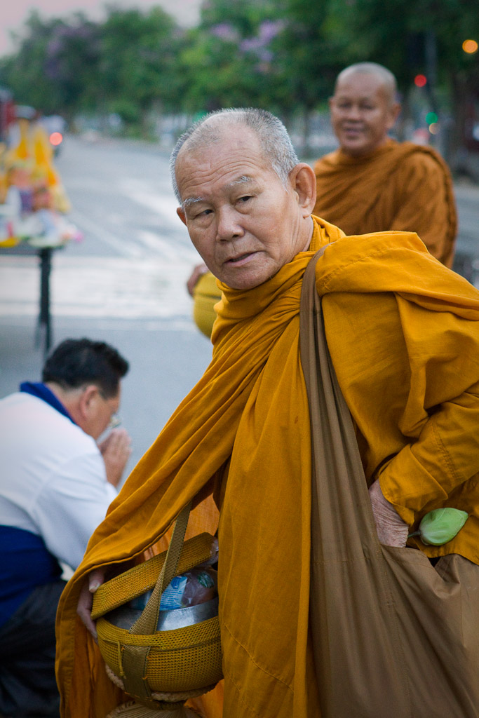 A monk receives alms on the streets in the early morning hours of the Songkran Festival.