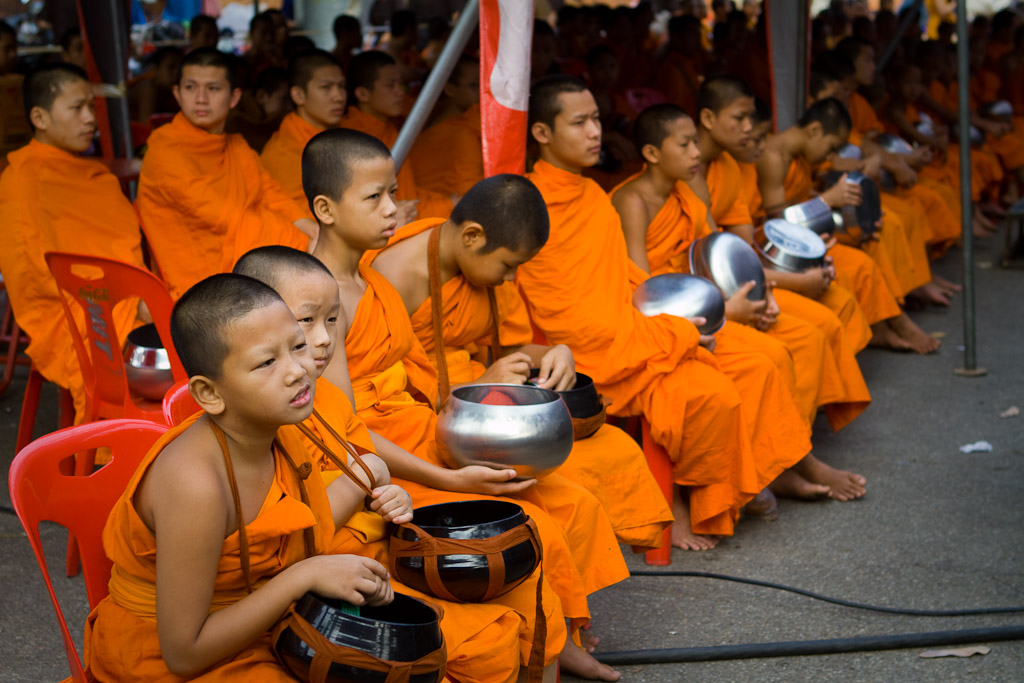 A young monk looks bored backstage while waiting for the start of the alms presentation that helps kick off Songkran.