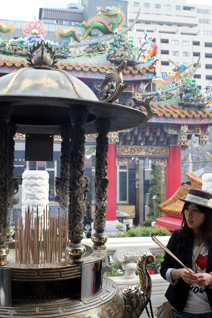 A girl places incense at a temple in Yokohama's Chinatown.