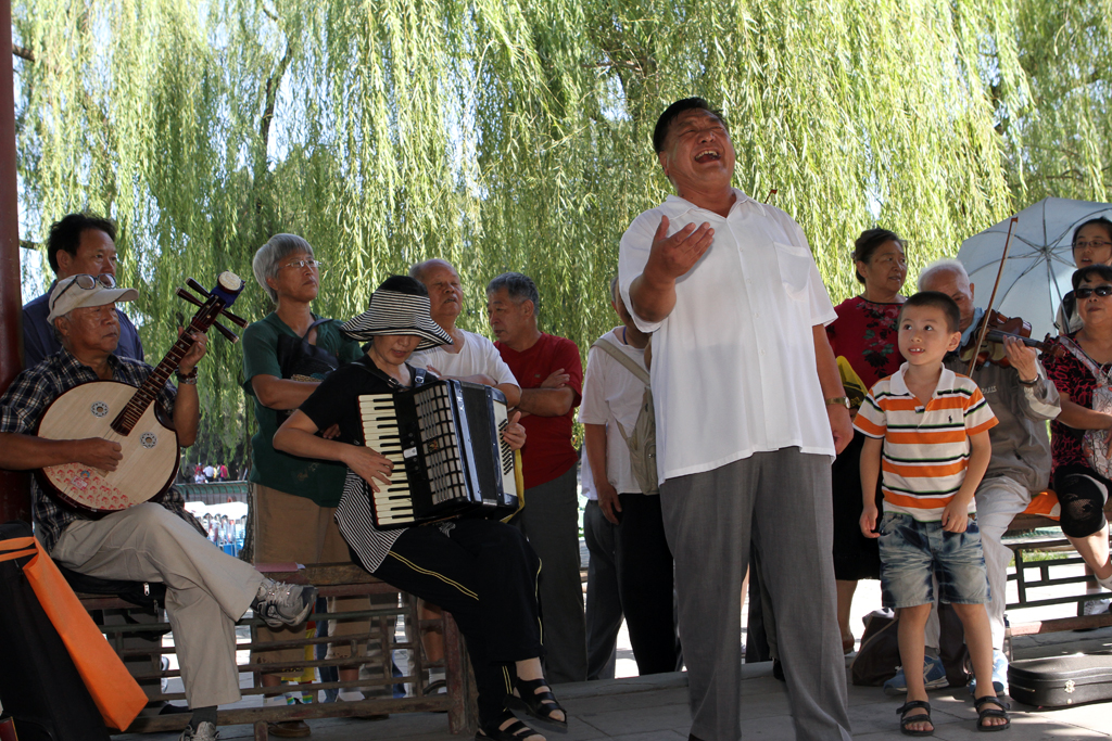 A group of onlookers surround an impromptu opera on an ordinary weekend at the park in Beijing.