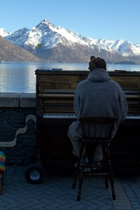 A busker plays piano by the lake in Queenstown.