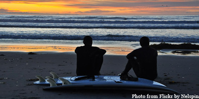 Surfers sit on the beach in San Diego.