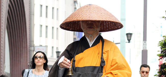 A Japanese monk inches his way along the streets of the Ginza district, Tokyo's equivalent to Rodeo Drive in Beverly Hills.