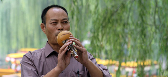 A Chinese musician plays a flute-like instrument at Beijing Summer Palace, the largest royal park in China.