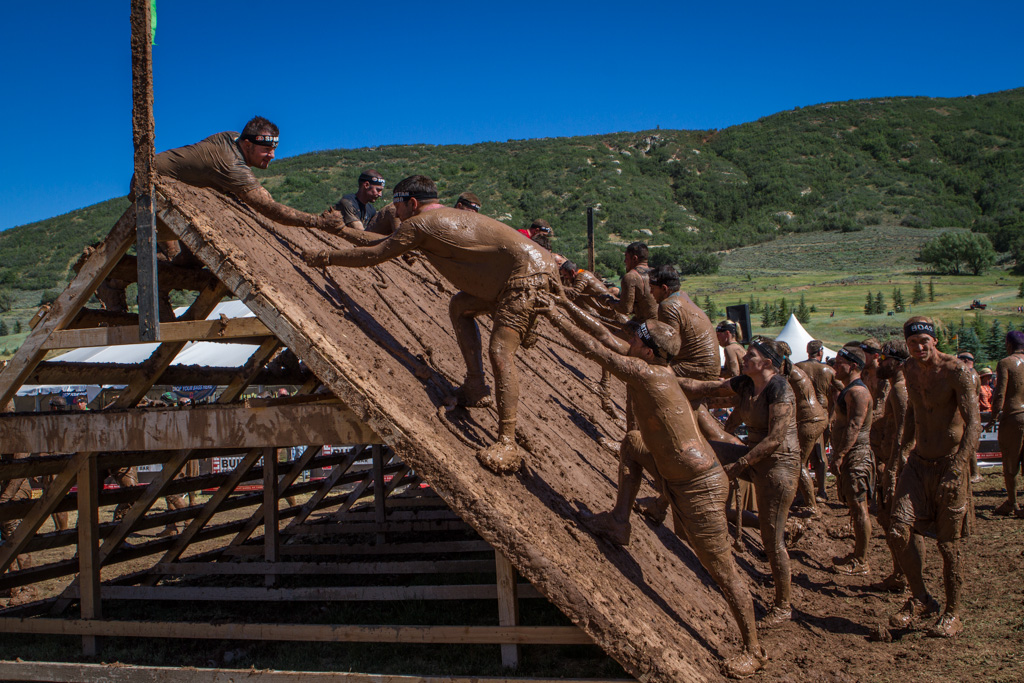 Exhausted participants help each other up and over the last real obstacle.