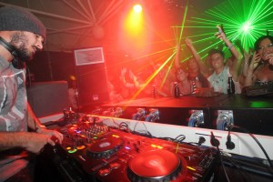 Zane lowe plays during radio one weekend at Privilege in Ibiza, Spain, with a crowd in front of him and lasers in the background
