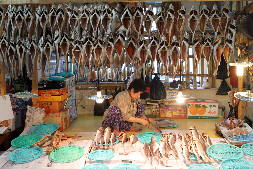 A woman cleans and prepares fish while others hang to dry above her.  Taken at the Fish Market in Busan, South Korea