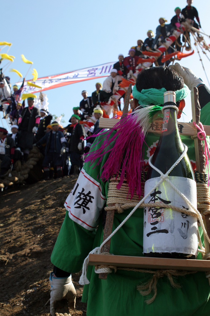 A man with a massive bottle of sake strapped to his back looks at the star of the Ombashira festival - the 20 meter long log loaded with people about to go down a giant hill.