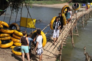 A bunch of travelers with inner tubes cross the Nam Sang river.