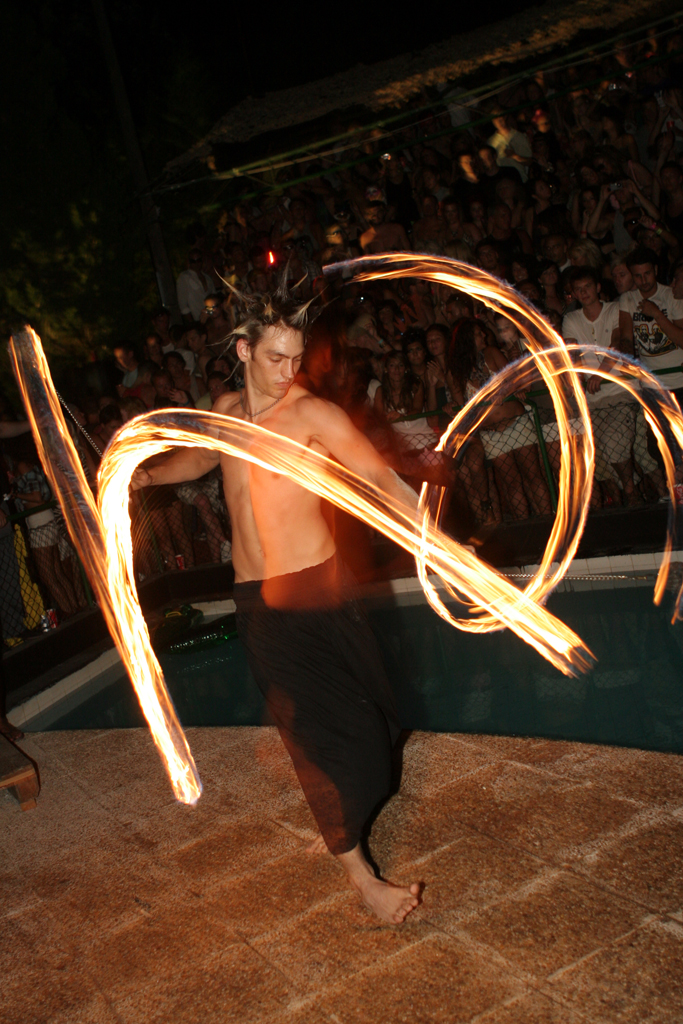 A fire dancer swings balls of fire around himself as he dances at the seal pit in Ibiza.