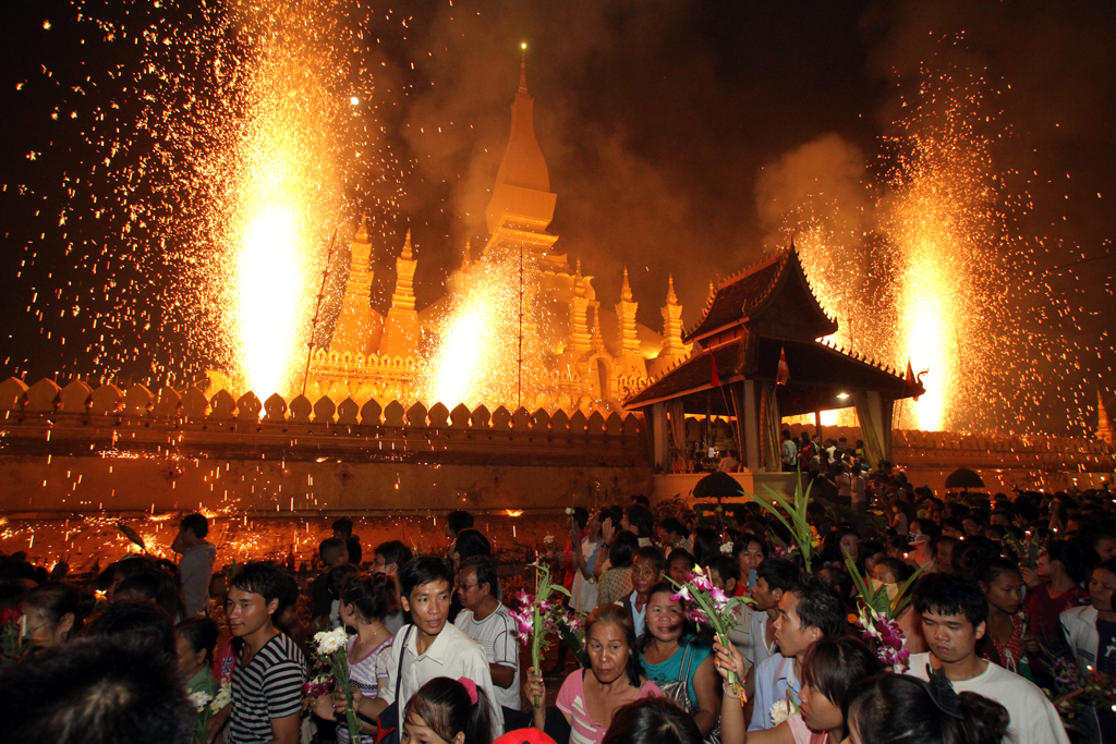 Fireworks go off at Bun Pha That Luang during the That Luang Festival, as people walk around the structure three times holding candles and offerings.