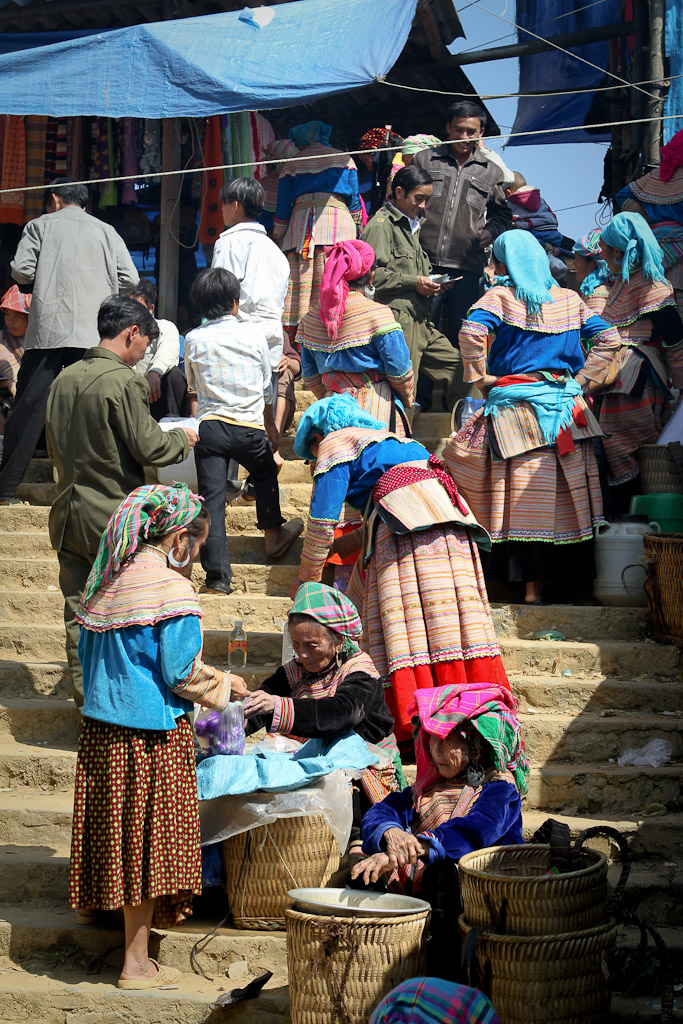 The women on this set of stairs are all selling home-brewed rice-based moonshine to shoppers at the Bac Ha Market, North Vietnam.
