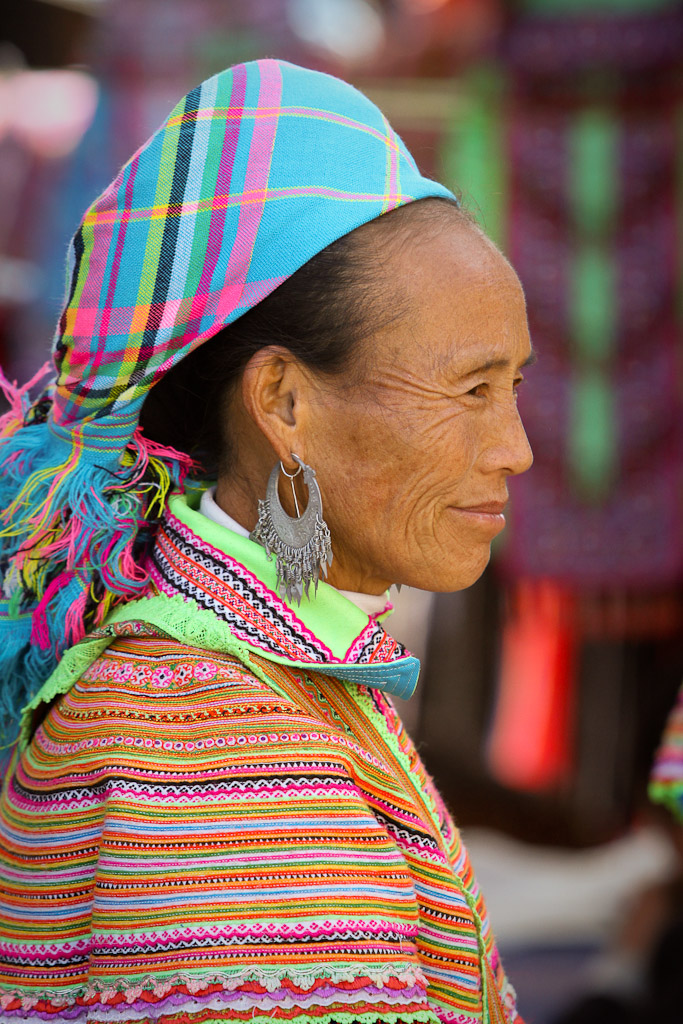 An elderly merchant dressed in very colorful, local garb.