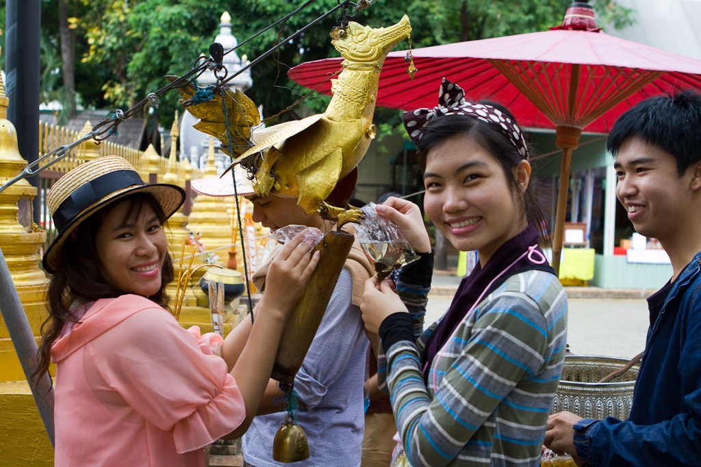 Aside from the water tossing, cleansing images of the Buddha is a major activity during Songkran. This group is filling a vessel with scented water that will take it to the Buddha image at the top of the wat.