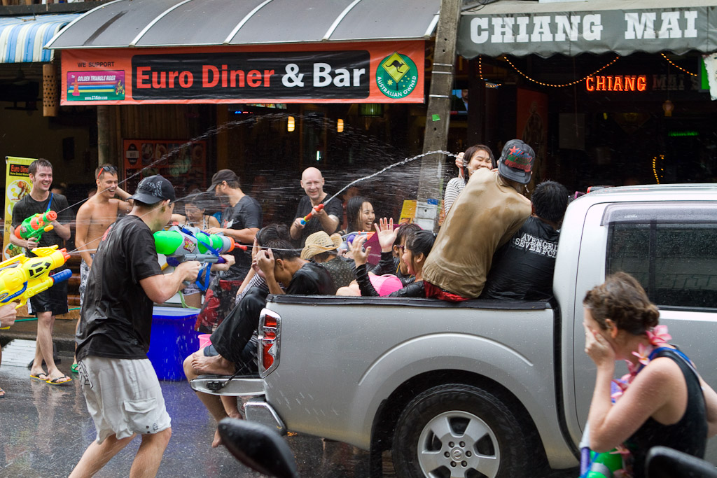 A truck full of locals pulls through an area packed with foreigners.