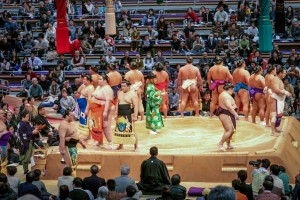 Sumo Wrestlers enter the sports arena and stand for the crowd.