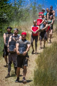 Spartan's bucket carry involves filling a bucket with rocks and carrying it up a hill and back.