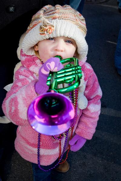 A little parade goer toots a horn at Mardi Gras, 2012