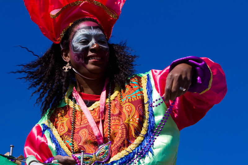 A member of a float throws beads to parade goers at Mardi Gras, 2012